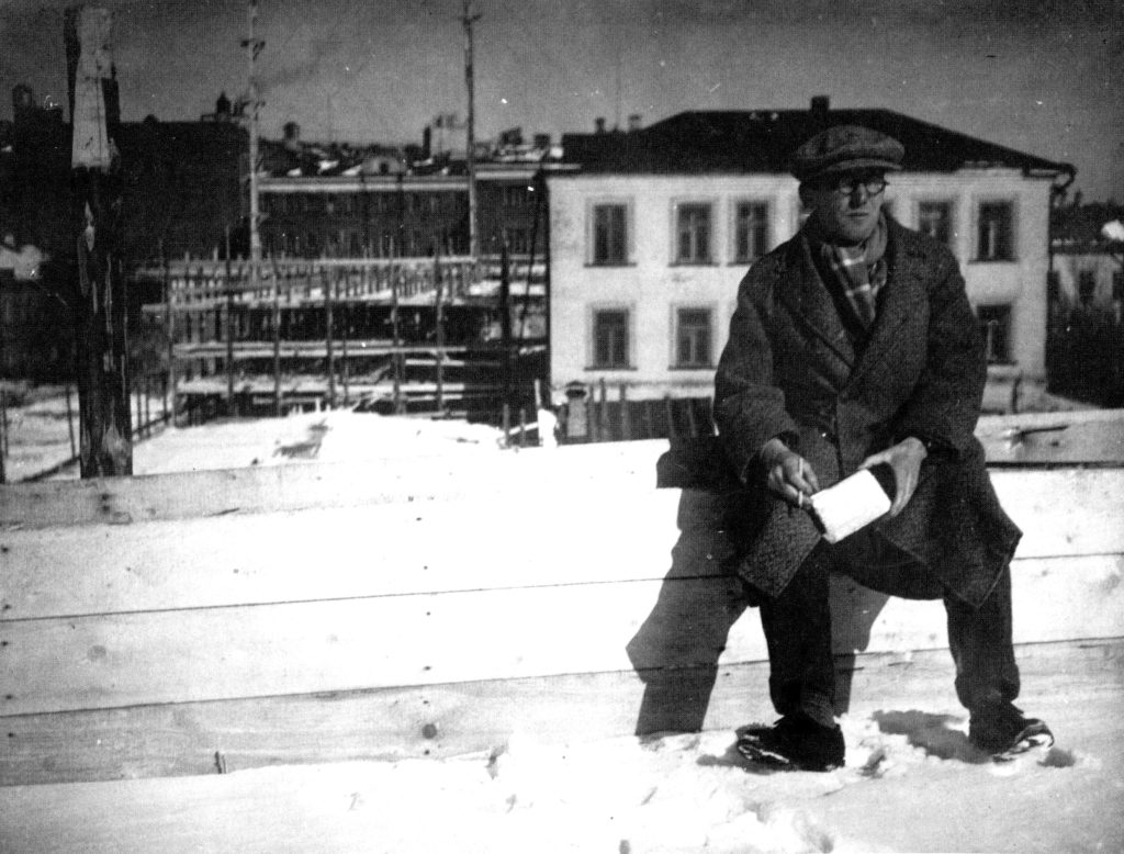 Le Corbusier sitting in front of the construction site for the tsentrosoiuz building in moscow_march 1931